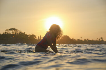 Indonesia, Bali, pregnant woman sitting on surfboard at sunset - KNTF02452