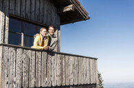 Couple leaning on balcony of a mountain hut, with arms around - UUF15955