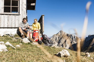 Hiking couple sitting in front of mountain hut, taking a break - UUF15961