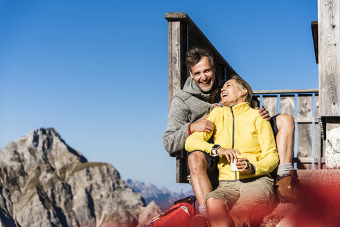 Hiking couple sitting in front of mountain hut, taking a break - UUF15970