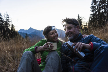 Hiking couple taking a break in the evening, wearing head lamps, drinking tea - UUF16042