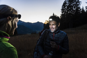 Couple hiking at night, wearing head lamps - UUF16045