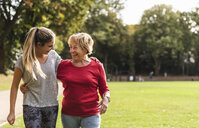 Granddaughter and grandmother having fun, jogging together in the park - UUF16051
