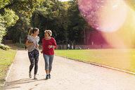 Granddaughter and grandmother having fun, jogging together in the park - UUF16057
