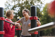 Grandmother and granddaughter training on bars in a park - UUF16063