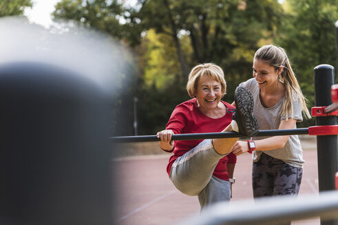Grandmother and granddaughter training on bars in a park - UUF16066