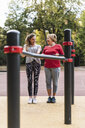 Grandmother and granddaughter training on bars in a park - UUF16069