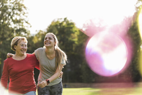 Granddaughter and grandmother having fun, jogging together in the park - UUF16075