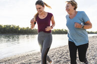 Granddaughter and grandmother having fun, jogging together at the river - UUF16081