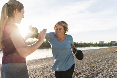 Grandmother doing boxing training with her graddaughter at the river - UUF16099