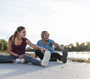 Grandmother and granddaughter sitting on ground at the river, warming up for training - UUF16105