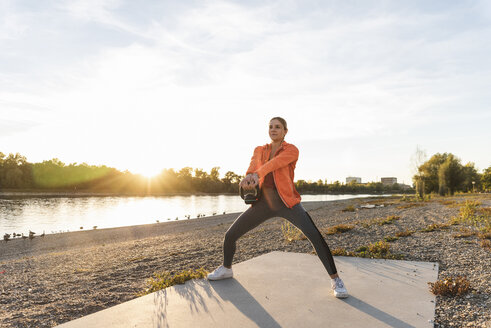 Young woman exercising with a kettlebell at the river - UUF16120