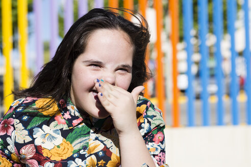 Teenager girl with down syndrome laughing, hand covering mouth - ERRF00265