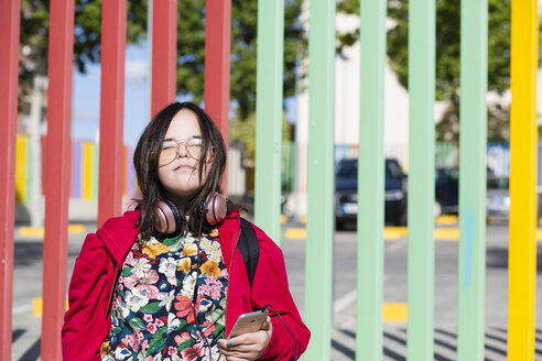 Teenager with down syndrome using smartphone, headphones, closed eyes - ERRF00268