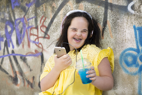 Teenager with down syndrome using smartphone, holding plastic cup - ERRF00271