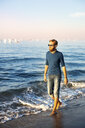 Young man walking at the beach in the evening - PUF01343