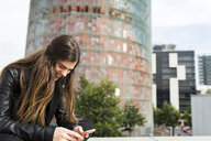 Spain Barcelona, happy young woman using cell phone in the city - VABF01955