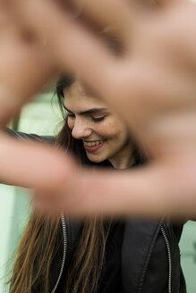 Happy young woman raising her hands - VABF01964