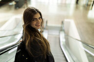 Portrait of smiling young woman on escalator - VABF01973