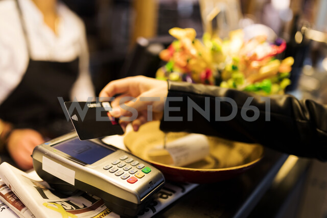 Close-up of woman paying with credit card at the counter - VABF01976