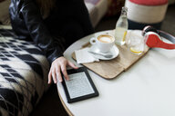 Close-up of young woman in a cafe using e-book - VABF01979