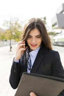 Young businesswoman using tablet and cell phone in the city - VABF01988