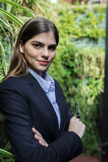 Portrait of confident young businesswoman surrounded by plants - VABF01991