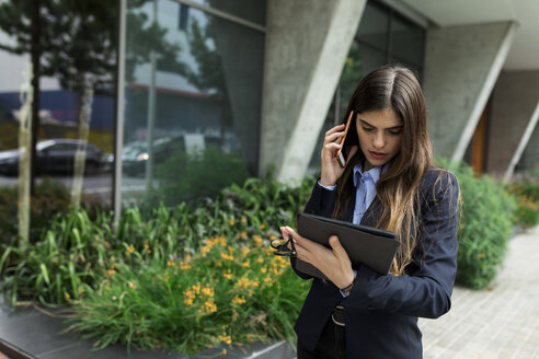 Young businesswoman using tablet and cell phone in the city - VABF02000