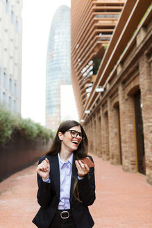 Happy young businesswoman holding cell phone in the city - VABF02003