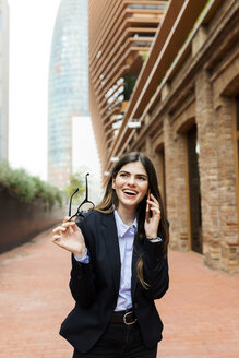 Happy young businesswoman on cell phone in the city - VABF02006