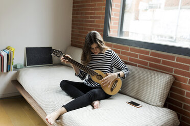 Young woman sitting on couch at home playing guitar - VABF02027