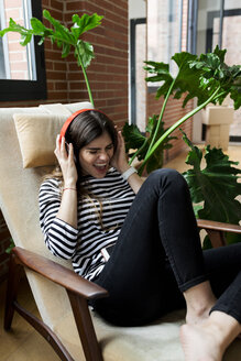 Excited young woman sitting in armchair at home listening to music with headphones - VABF02036