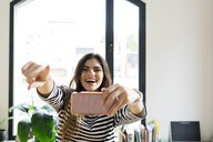 Happy young woman at home taking a selfie - VABF02039