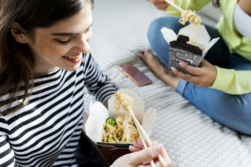 Two happy young women having Asian takeaway food at home - VABF02045