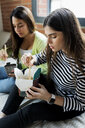 Two young women having Asian takeaway food at home - VABF02048