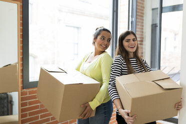 Portrait of two smiling young women carrying cardboard boxes in new apartment at the window - VABF02051