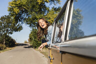 Pretty woman on a road trip with her camper, looking out of car window - UUF16129