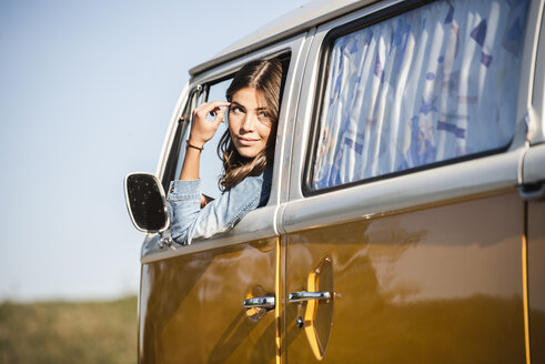 Pretty woman on a road trip with her camper, looking out of car window - UUF16132