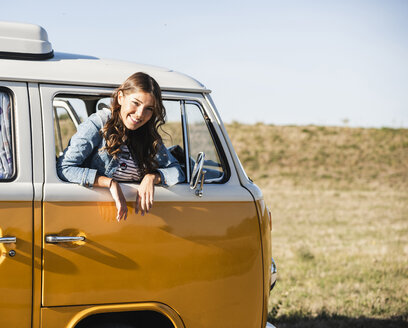 Pretty woman on a road trip with her camper, looking out of car window - UUF16135