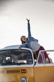 Pretty woman on a road trip with her camper, cheering, enjoying freedom - UUF16150