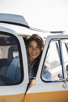Pretty woman on a road trip with her camper, looking out of car window - UUF16153