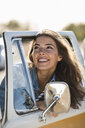 Pretty woman on a road trip with her camper, looking out of car window - UUF16156
