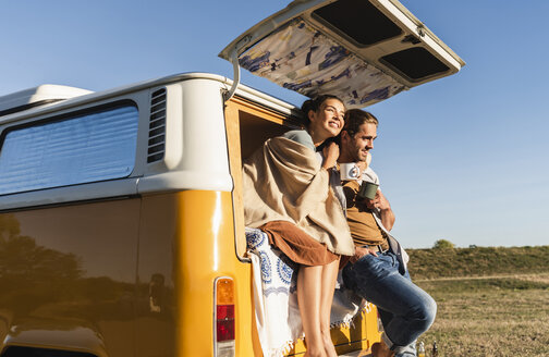 Happy couple doing a road trip with their camper, sitting on their bed, drinking coffee - UUF16192