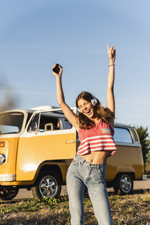 Pretty woman on a road trip with her camper, dancing, listening music - UUF16234