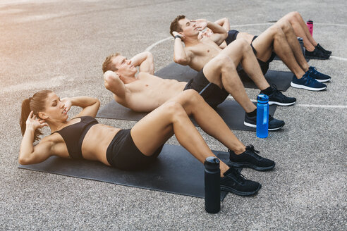 Sporty team of two women and two men, situps - HMEF00136