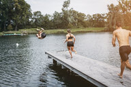 Sportive people running on jetty, jumping into lake after workout training - HMEF00163
