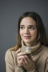 Portrait of smiling woman wearing light brown turtleneck pullover holding glass of coffee - MOEF01828