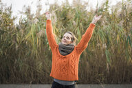 Portrait of smiling woman wearing orange knit pullover and scarf in autumn - MOEF01831