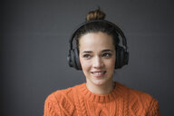Portrait of smiling woman with headphones wearing orange knit pullover against grey background - MOEF01843