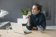 Portrait of content woman with laptop and credit card sitting at desk at home - MOEF01852